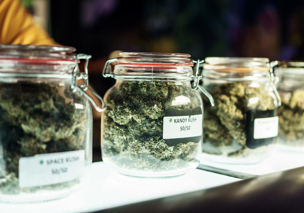 A dispensary worker vending jars of cannabis