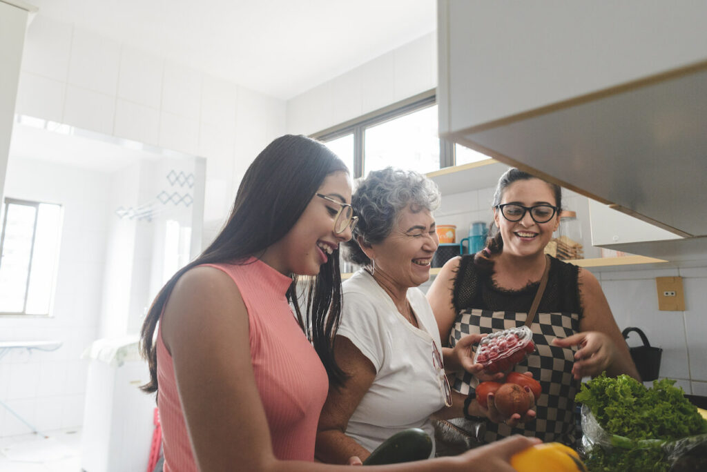 Latina grandmother, mother, and daughter unpacking groceries in the kitchen