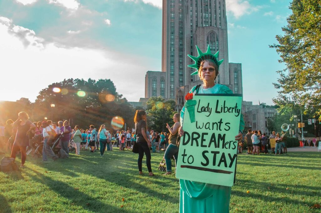 """Person dressed as lady liberty standing in park with sign; sign reads """"lady liberty wants dreamers to stay. """""""