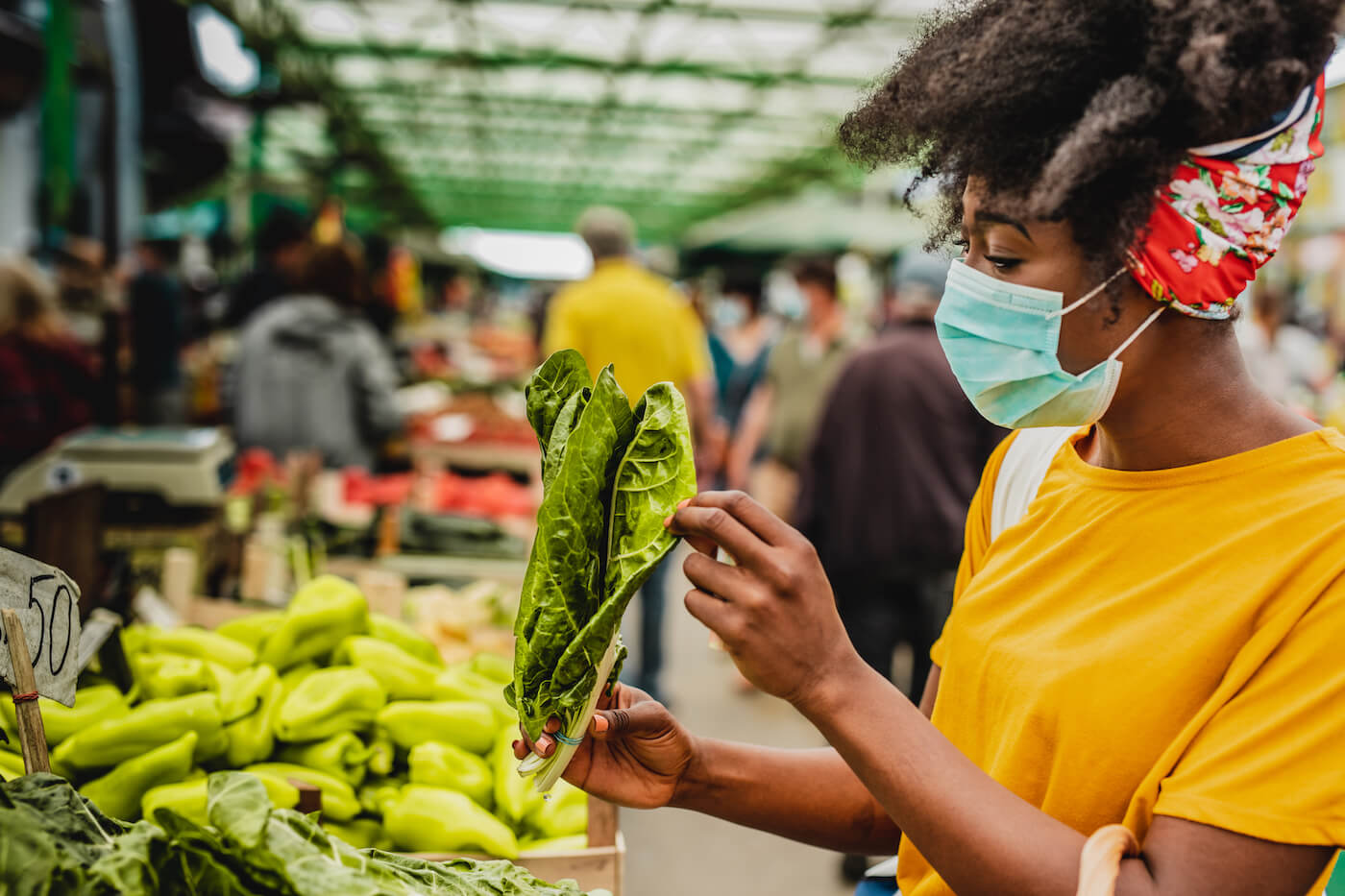 Young african american woman with face mask inspecting kale at farmers market