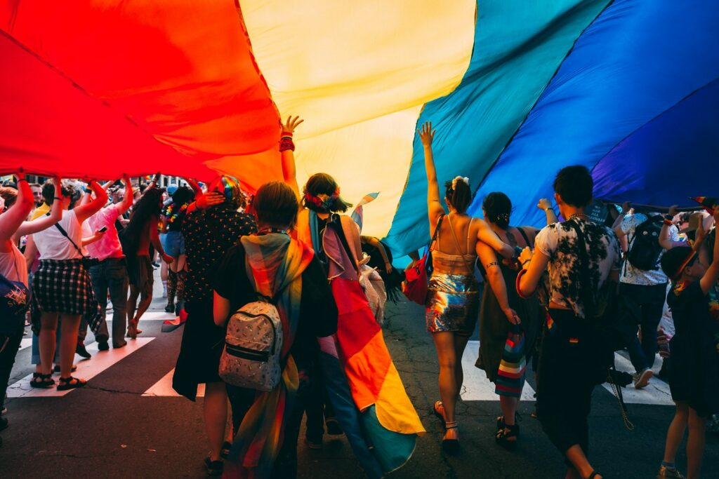 Group of people under rainbow flag at pride parade
