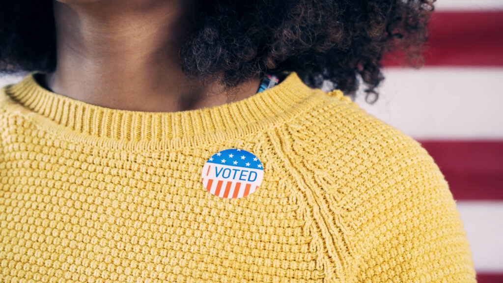 """Black person in yellow sweater wearing """"i voted"""" sticker; american flag in background"""