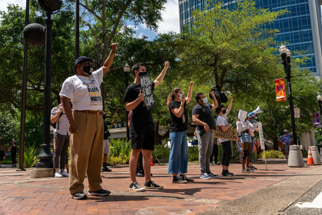"""A multiracial group of 6 demonstrators stand with fist raised in front of jacksonville, florida city hall. Visible signs read, """"protest is not a crime,"""" and """"black lives matter. """""""