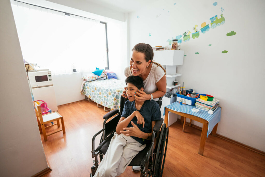 Latina mother massaging her son, who has celebral palsy