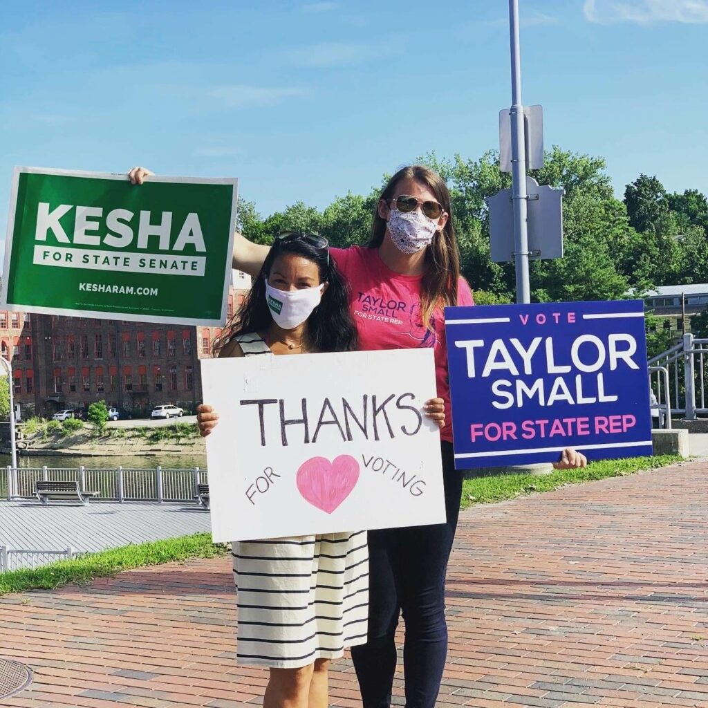 """Vermont legislators kesha ram and taylor small hold signs reading, """"thanks ❤️,"""" """"taylor small for state rep,"""" and """"kesha for state senate. """""""