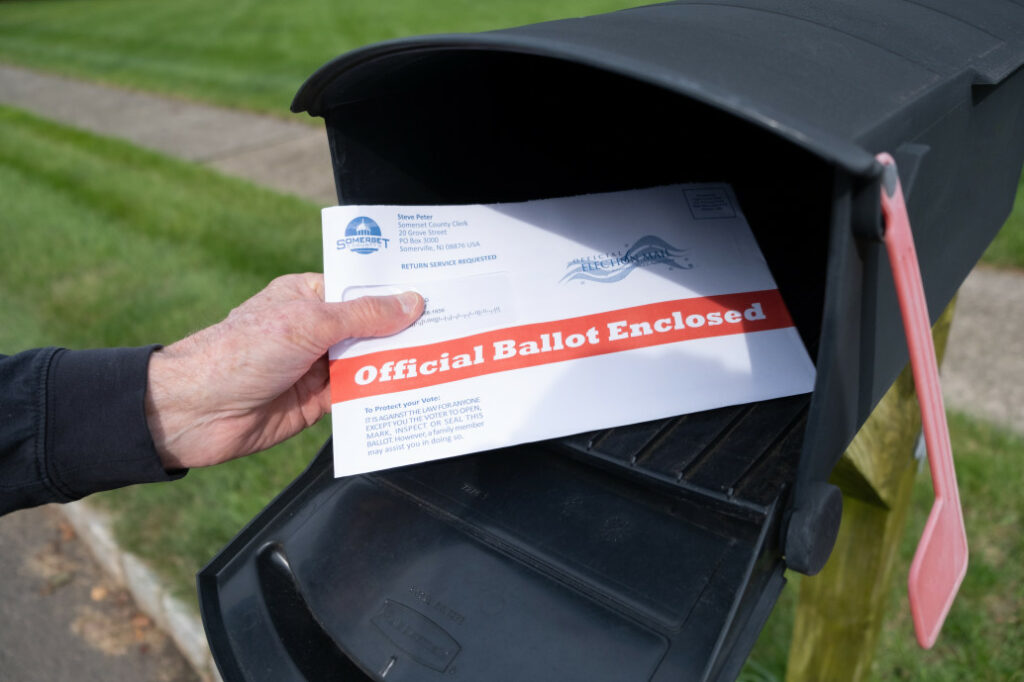 Person placing a mail-in ballot into a mailbox