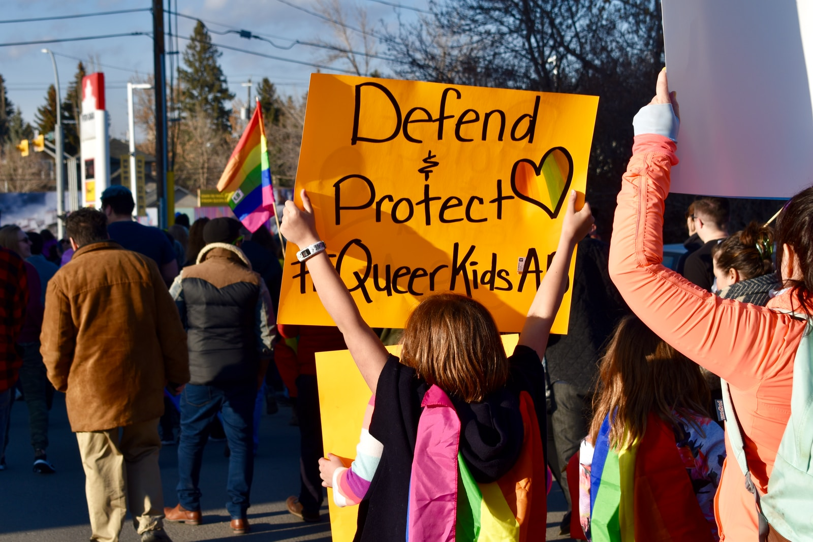 """Peoosn holding printed orange paper that reads """"defend + protect queer kids"""""""