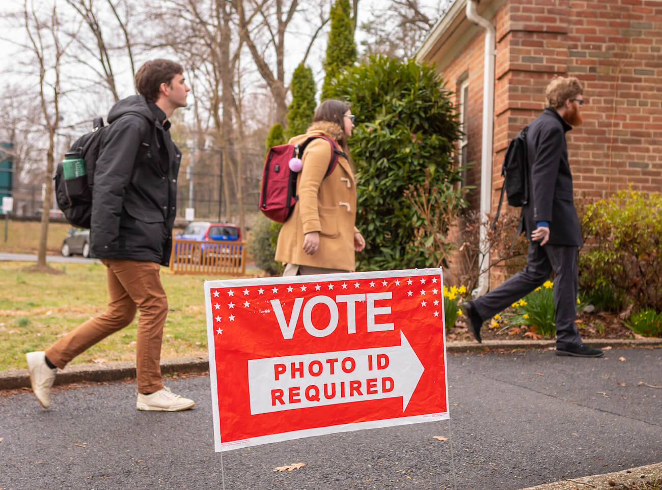 """Three white primary election voters arrive at polling place in arlington virginia. Sign reads, """"vote. Photo id required. """""""