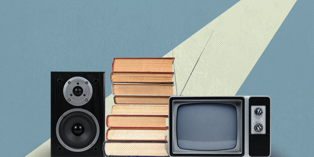 A spotlight shines on a stereo, stack of books, and old school television