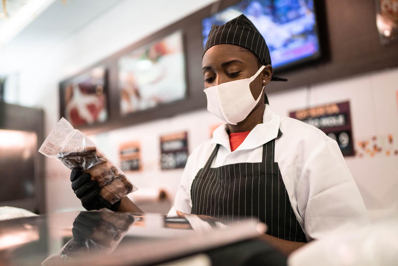 Black butcher talking to customer at butchers shop