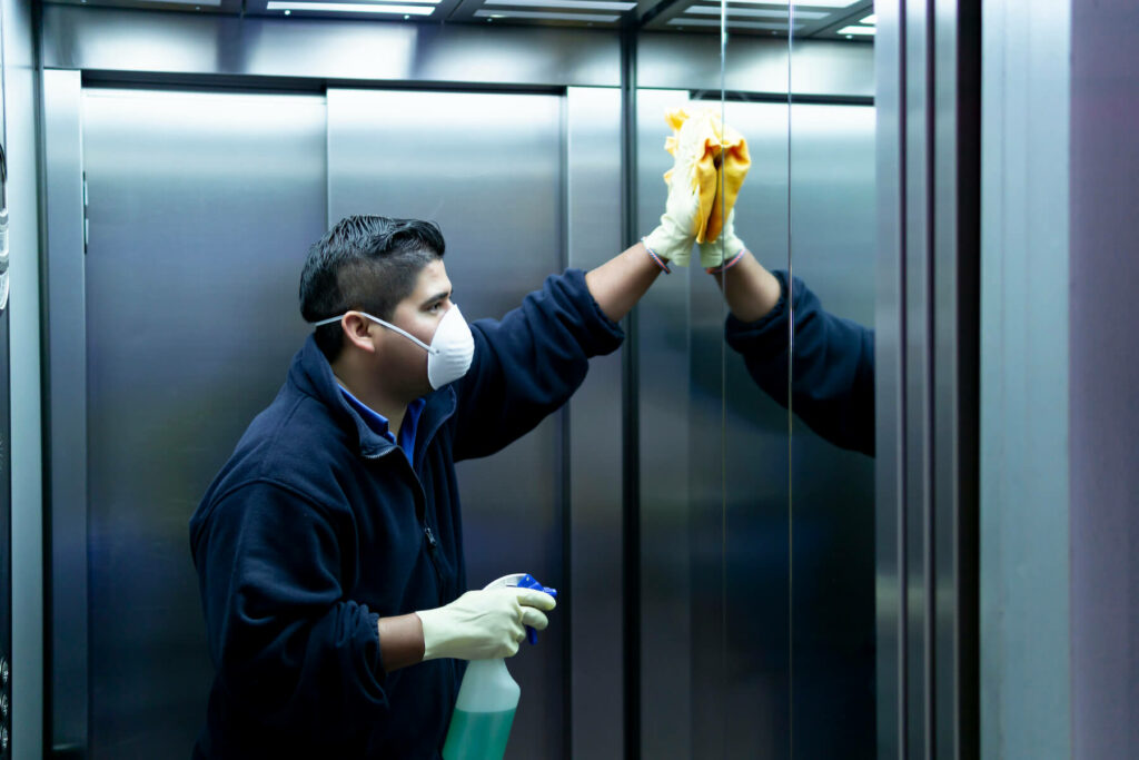 Cleaning staff disinfecting elevator