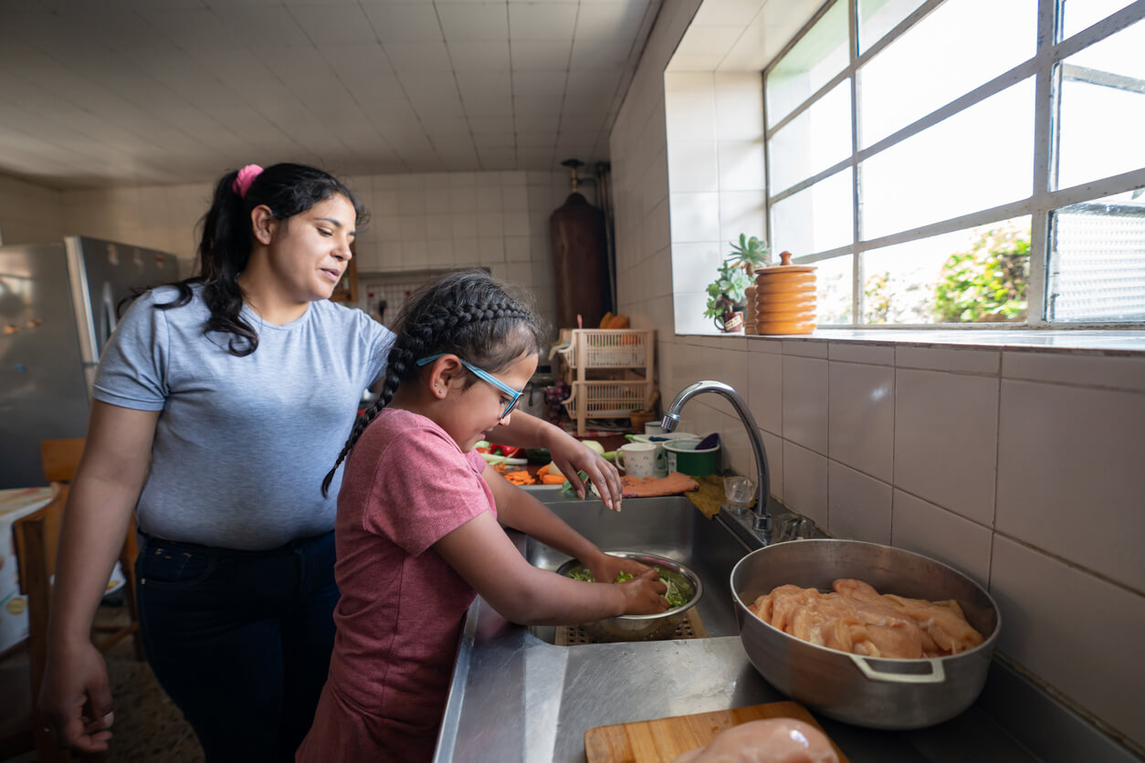 Latina mother teaches daughter how to wash vegetables in kitchen sink
