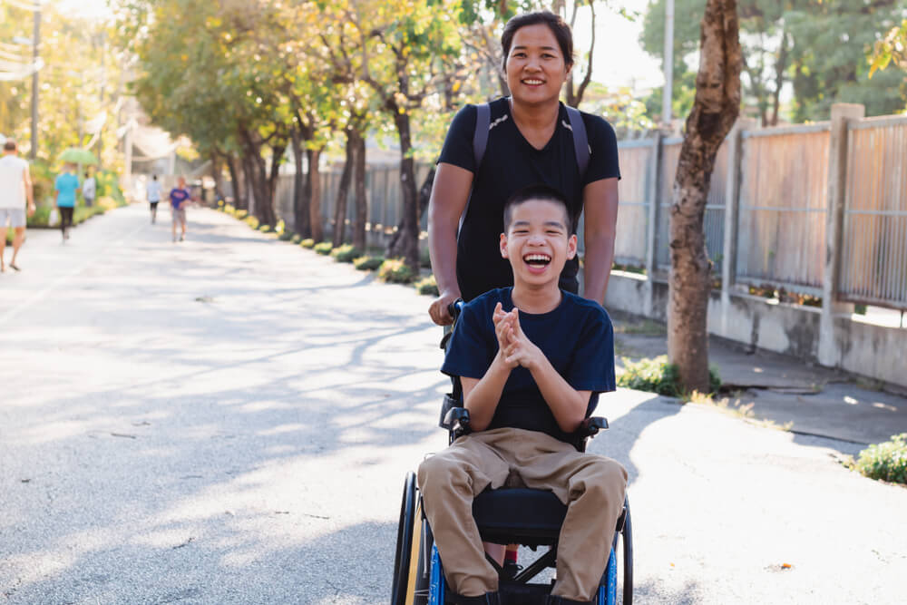 Young asian child in wheelchair laughs with caretaker or family member at the park