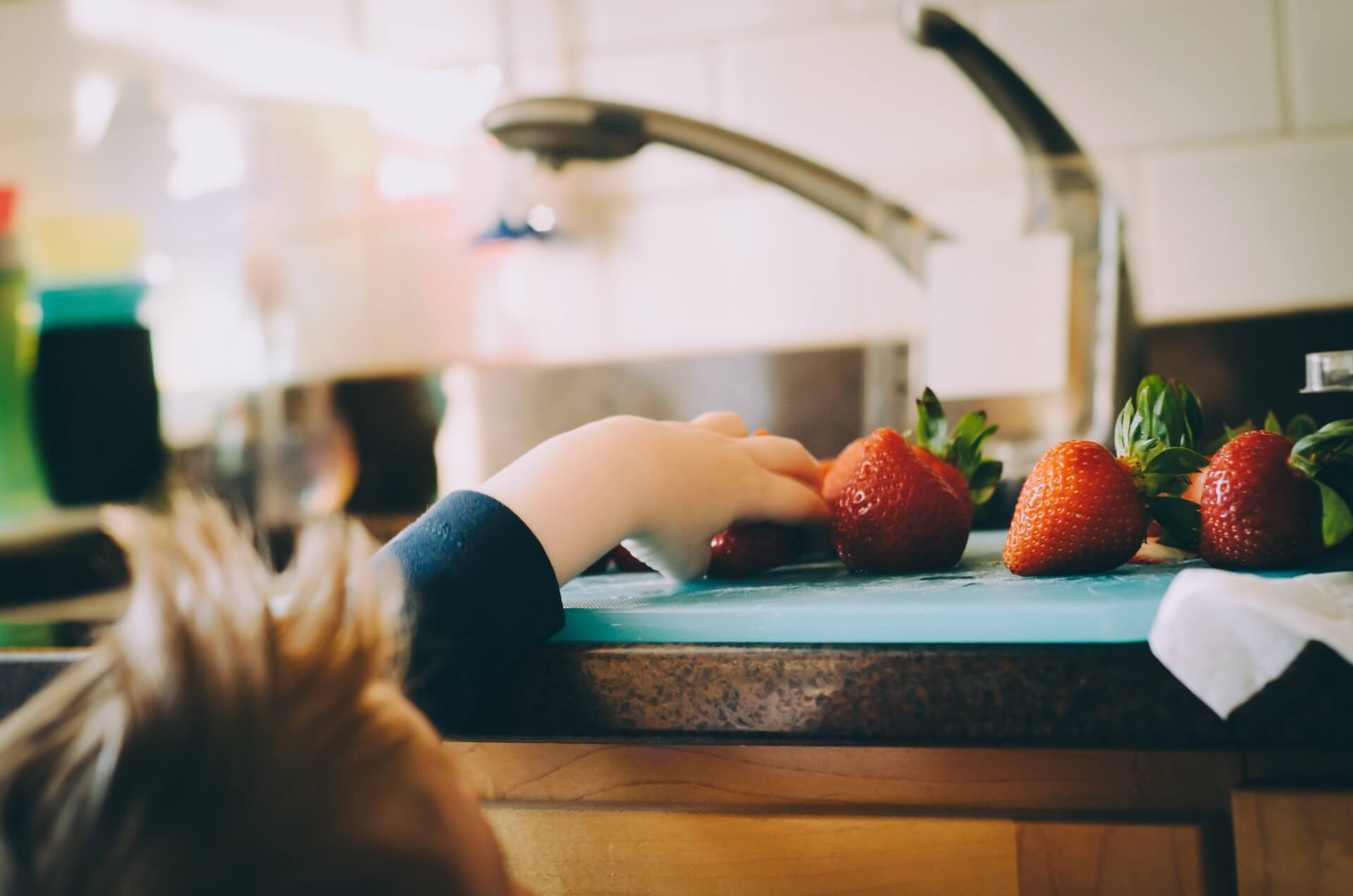 Child reaching for strawberries on kitchen counter