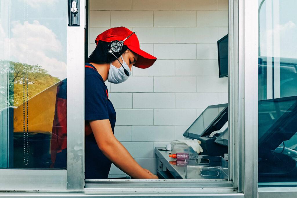Fast food worker wearing masks opens cash register at drive-through window gumpanat / shutterstock. Com