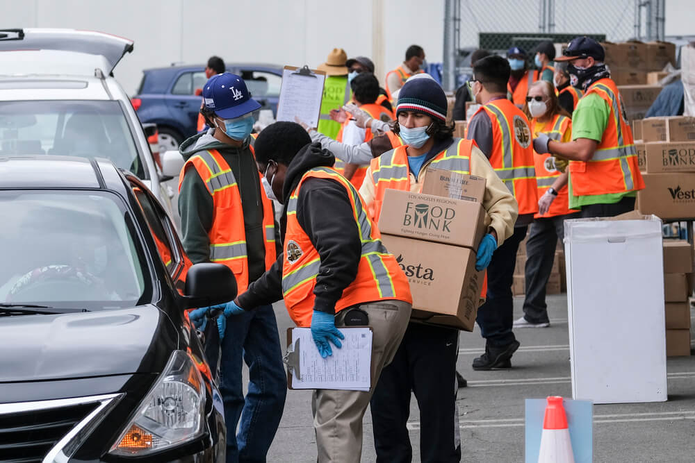 Volunteers load food into the trunk of vehicles during a ''let's feed l. A. County'' drive thru food distribution by the los angeles regional food bank, april 23, 2021, in rosemead, california. Ringo chiu / shutterstock. Com